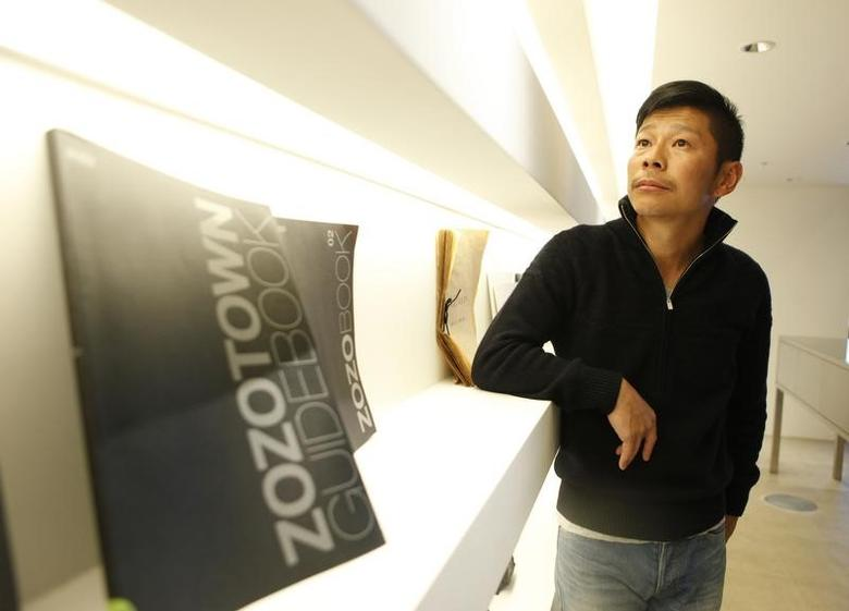 Yusaku Maezawa, chief executive of online fashion retailer Start Today Co, poses next to a catalogue of his online shopping site ''Zozotown'' after an interview with Reuters at the company headquarters in Chiba, east of Tokyo, March 27, 2012. A commitment to innovation and a laser-like focus on making consumers happy are shared traits experts agree set off Japan's emerging successes from once-proud but now-struggling firms such as Sony and Panasonic. Experts say more such success stories - found in sectors ranging from retail, Internet and mobile games to niche manufacturers - could help revive a Japanese economy stuck in the doldrums for decades and saddled with an ageing population. Picture taken March 27, 2012. To match Insight JAPAN/BUSINESS-SUCCESSES   REUTERS/Toru Hanai