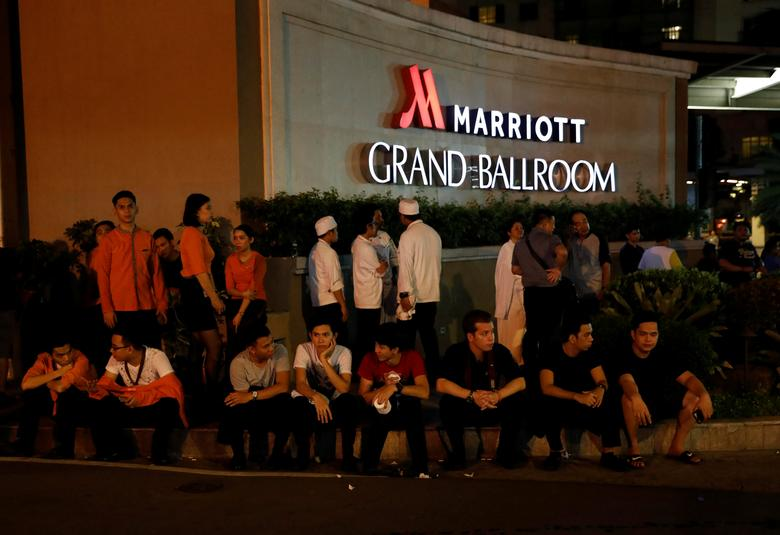 Evacuated employees are seen at the entrance of a hotel near a situation at a Resorts World building in Pasay City, Metro Manila, Philippines June 2, 2017. REUTERS/Erik De Castro
