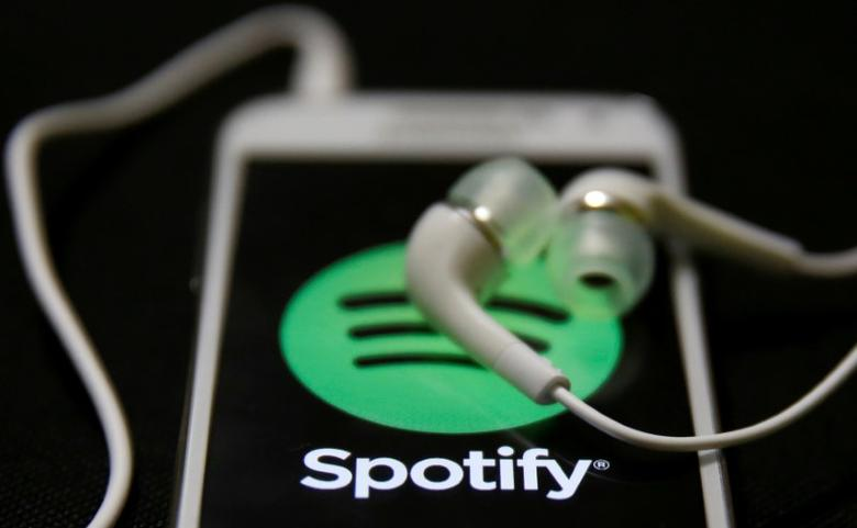 FILE PHOTO: Earphones are seen on top of a smart phone with a Spotify logo on it in this February 20, 2014 photo illustration. REUTERS/Dado Ruvic/Illustration/File Photo