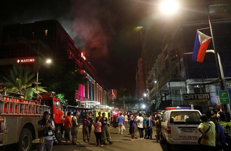 Evacuated employees and guests of hotels stand along a road and watch as smoke billows from a Resorts World building in Pasay City, Metro Manila, Philippines June 2, 2017. REUTERS/Erik De Castro