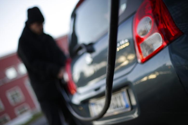 A man fills up his car at a petrol station in Rome January 6, 2015. REUTERS/Max Rossi/Files