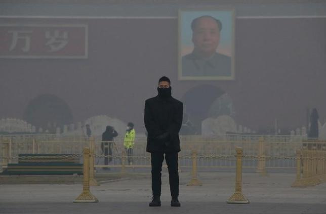 A member of the security personnel wearing a mask stands guard in the smog at Tiananmen Square after a red alert was issued for heavy air pollution in Beijing, China, December 20, 2016. REUTERS/Jason Lee/Files