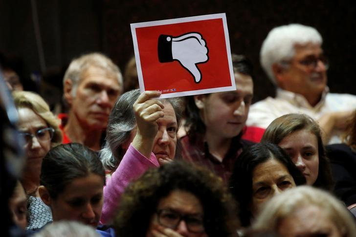 A voter holds up a sign during a town hall meeting with constituents by U.S. Representative Leonard Lance (R-NJ) in Cranford, New Jersey, U.S., May 30, 2017. REUTERS/Mike Sega/Files