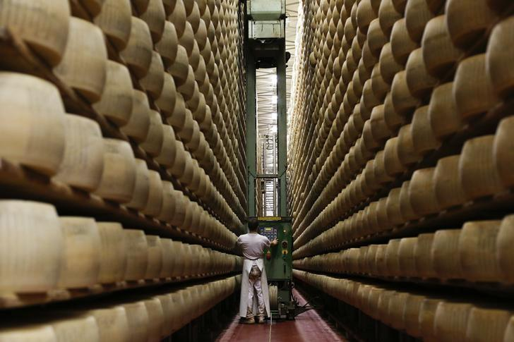 A worker inspects wheels of Parmesan cheese at storehouse shelf 4 Madonne Caseificio dell'Emilia dairy cooperative in Modena, Italy, February 16 2016.REUTERS/Alessandro Bianchi