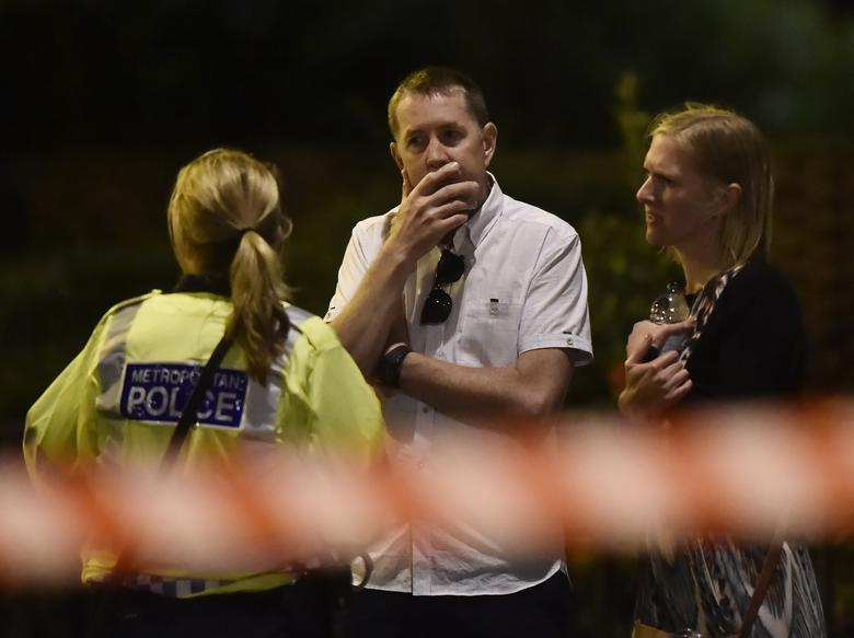 People speak with a police officer after an incident near London Bridge.  REUTERS/Hannah Mckay