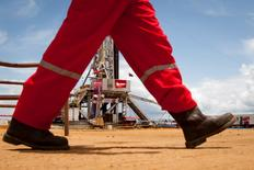FILE PHOTO: An oil worker walks past a drilling rig at an oil well operated by Venezuela's state oil company PDVSA in Morichal July 28, 2011. REUTERS/Carlos Garcia Rawlins/File Photo