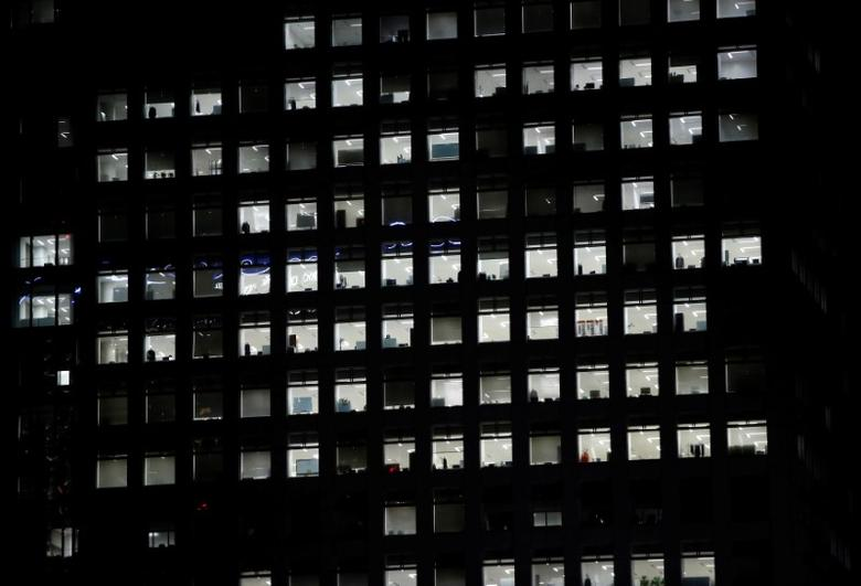 FILE PHOTO: Office lighting is seen through windows of a high-rise office building in Tokyo July 31, 2014.  REUTERS/Issei Kato/File Photo