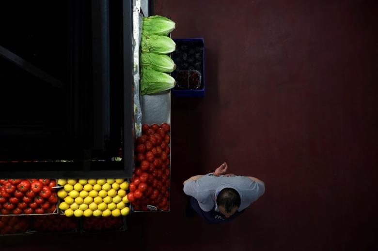 FILE PHOTO: A grocer waits for customers next to his stand at a food market in Madrid, Spain, May 17, 2017. REUTERS/Susana Vera/File Photo