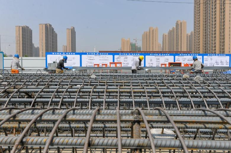 Workers weld reinforcement bar at a construction site in Zhengzhou, China June 2, 2017. REUTERS/Stringer