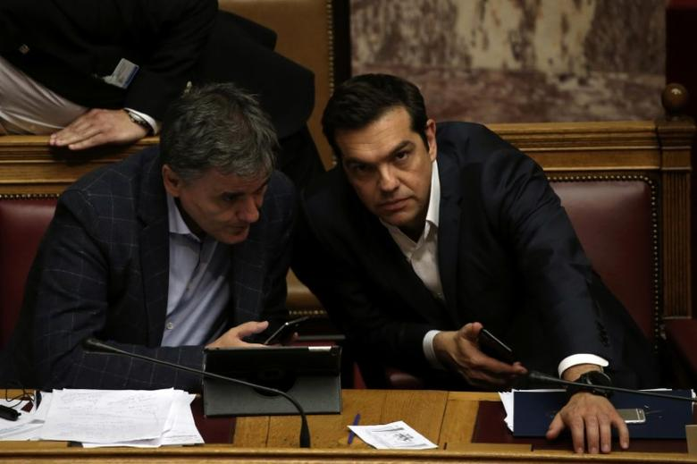 FILE PHOTO: Greek Prime Minister Alexis Tsipras and Finance Minister Euclid Tsakalotos attend a parliamentary session before a vote on the latest round of austerity Greece has agreed with its lenders, in Athens, Greece, May 18, 2017. REUTERS/Alkis Konstantinidis