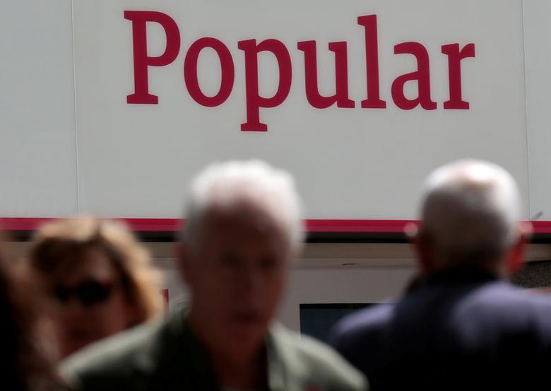 FILE PHOTO: People walk past a branch of Spain's Banco Popular in Madrid, Spain, May 26, 2016. REUTERS/Andrea Comas/File Photo