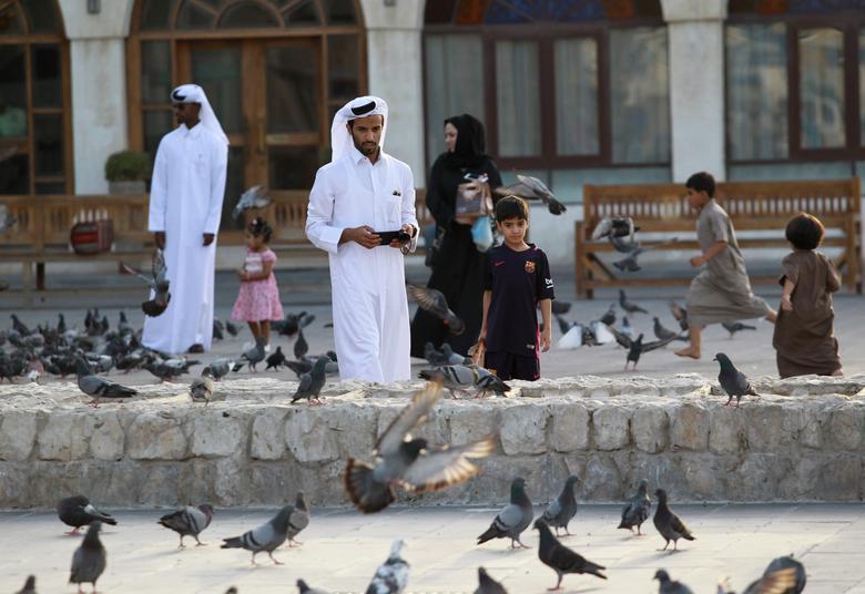 People look at pigeons at Souq Waqif market in Doha, Qatar, June 6, 2017. REUTERS/Naseem Zeitoon