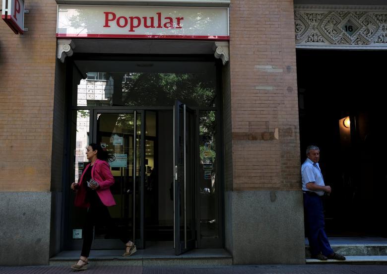 FILE PHOTO: A woman leaves a Banco Popular branch in Madrid, Spain, June 6, 2017. REUTERS/Juan Medina
