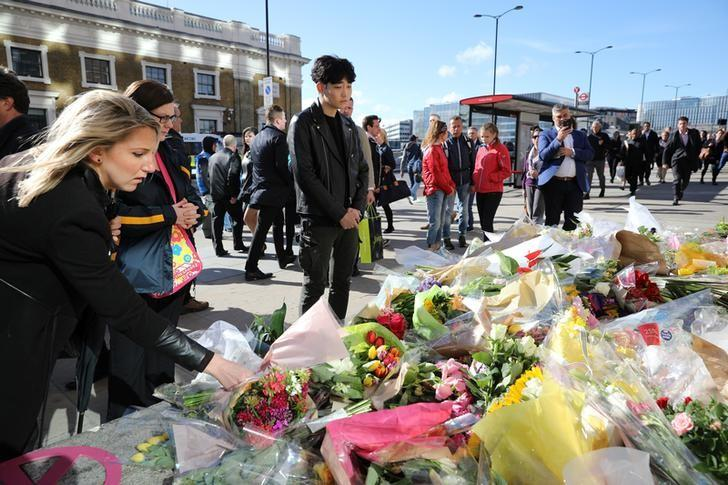 Pedestrians walk over London Bridge, and look at floral tributes, near the scene of the recent attack on London Bridge and Borough Market, London, Britain June 6, 2017. REUTERS/Marko Djurica