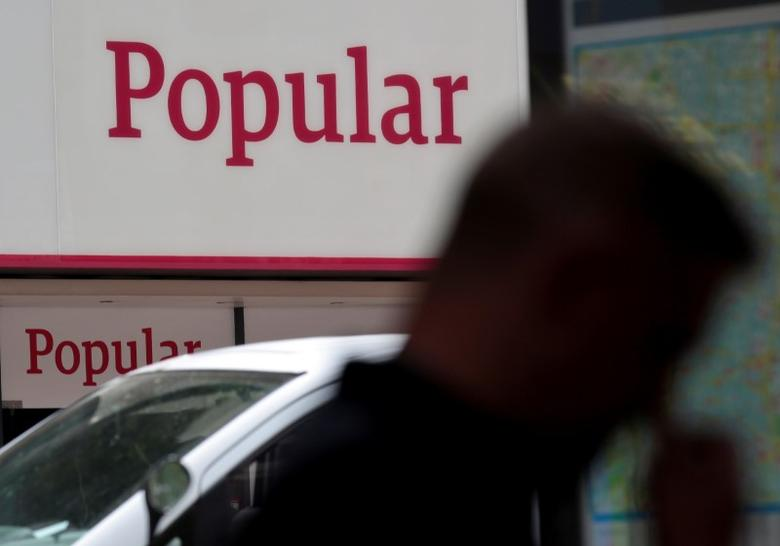 A man walks past a branch of Spain's Banco Popular in Madrid, Spain, May 26, 2016. REUTERS/Andrea Comas/File Photo