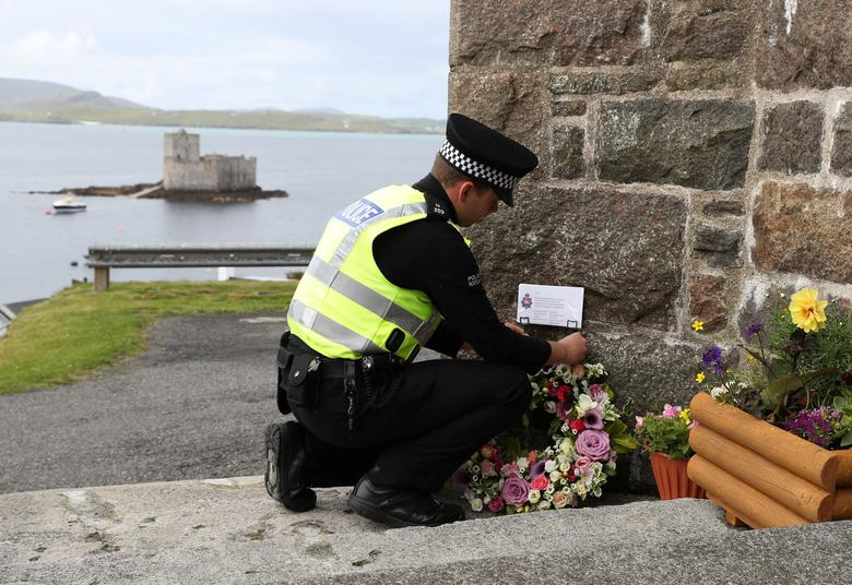 Flowers are laid by an officer from Police Scotland outside the Church of Our Lady, Star of the Sea, ahead of the funeral of Manchester bomb victim Eilidh MacLeod, in Castlebay on the island of Barra, in Scotland June 5, 2017.    REUTERS/Andrew Milligan/Pool