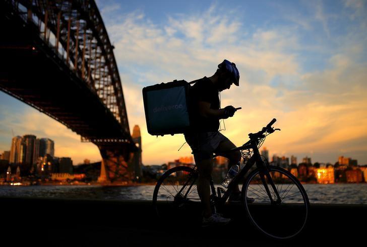 资料图片:2016年10月,澳洲,夕阳映照的悉尼港大桥下,一名快递员在低头查看手机上的信息。REUTERS/Steven Saphore