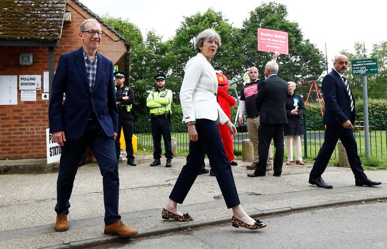 Britain's Primer Minister Theresa May and her husband Philip walk past the Give Me Back Elmo candidate as they leave a polling station in Sonning, Britain, June 8, 2017. REUTERS/Eddie Keogh