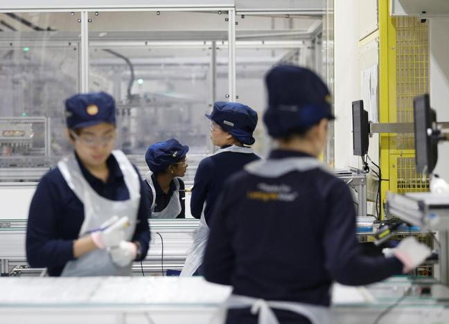 Employees work at a production line during a tour of an REC solar panel manufacturing plant in Singapore May 5, 2017. Edgar Su