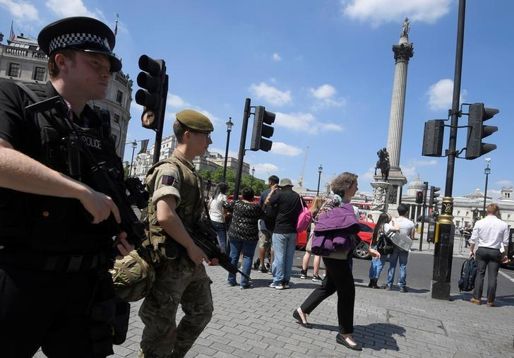 A soldier and a police officer walk past Trafalgar Square during a mobile patrol in central London, May 25, 2017. REUTERS/Toby Melville