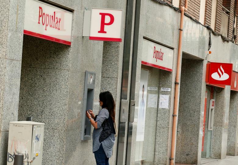 A woman uses a Banco Popular's cash dispenser (ATM) next to a Santander office in Barcelona, Spain June 7, 2017. REUTERS/Albert Gea
