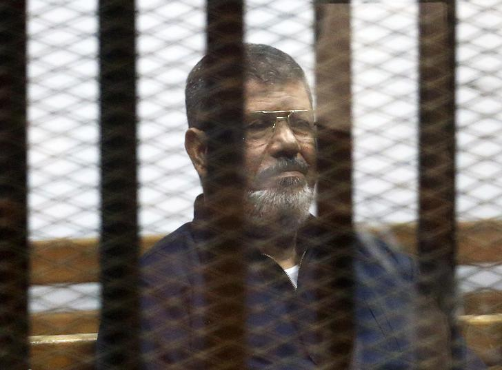 FILE PHOTO - Deposed Egyptian President Mohamed Mursi listens to his verdict behind bars at a court on the outskirts of Cairo, Egypt June 16, 2015. REUTERS/Asmaa Waguih/File Photo