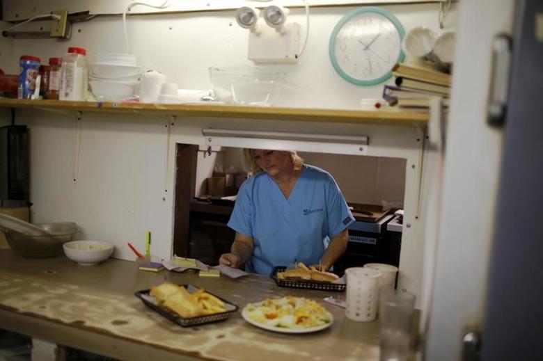 A waitress waits for plates in the kitchen of a restaurant in Bayou La Batre, Alabama November 10, 2009. REUTERS/Carlos Barria