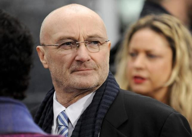 British musician Phil Collins watches his daughter British actress Lily Collins (not pictured) as he arrives at the Hollywood world premiere of ''Mirror Mirror'' in Los Angeles, California March 17, 2012. REUTERS/Gus Ruelas
