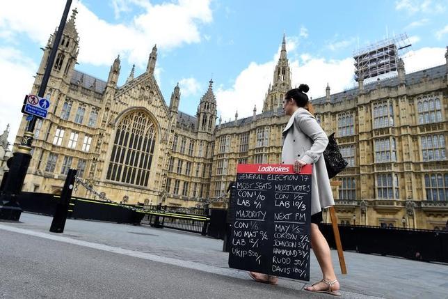 6月8日、ノムラのロンドンのアナリストらは英総選挙(下院、定数650)について、出口調査と最初に勝敗が確定した2議席の結果に基づき、メイ首相率いる与党保守党が331議席を獲得し、過半数を確保するとの見通しを示した。賭け率を書いた表を持って議会前を歩く賭け業者の女性、7日撮影(2017年 ロイター/Clodagh Kilcoyne)
