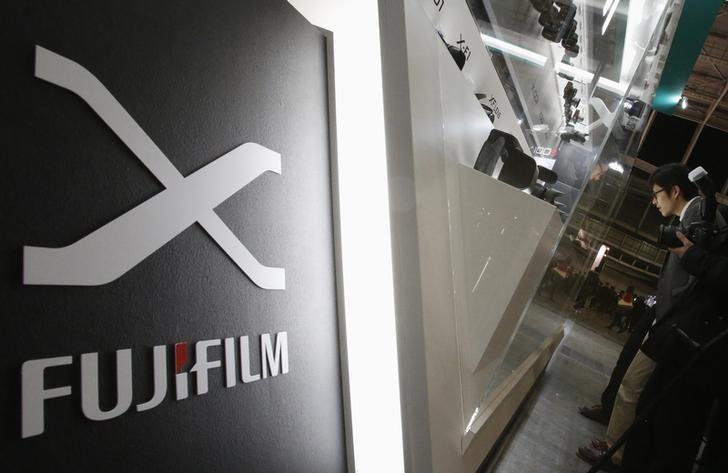 A visitor looks at Fujifilm's digital cameras at the Camera & Photo Imaging Show 2013 in Yokohama, south of Tokyo January 31, 2013. REUTERS/Yuya Shino/Files