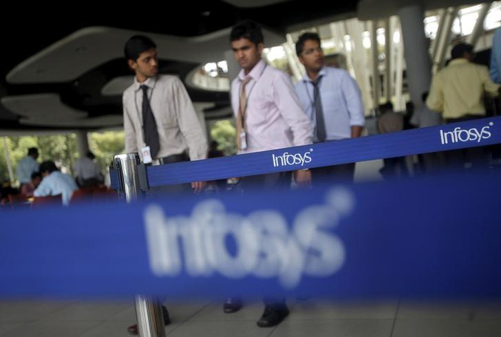 FILE PHOTO: Employees of Indian software company Infosys walk past Infosys logos at their campus in the Electronic City area in Bengaluru, India, September 4, 2012. REUTERS/Vivek Prakash/File photo
