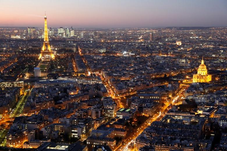FILE PHOTO: A general view shows the illuminated Eiffel Tower (L), the Hotel des Invalides (R) and rooftops at night in Paris, France, November 28, 2016.   REUTERS/Charles Platiau/File Photo
