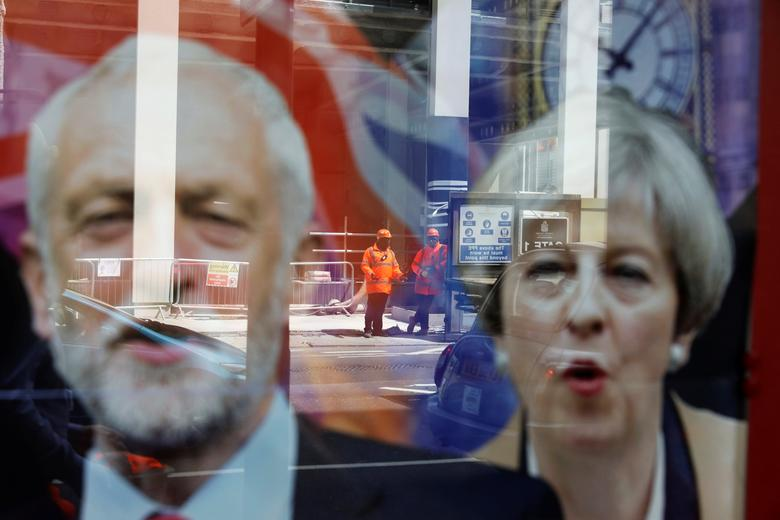 Workers in protective equipment are reflected in the window of a betting shop with a display inviting customers to place bets on the result of the general election with images of Britain's Prime Minister Theresa May and opposition Labour Party leader Jeremy Corbyn, in London, June 7, 2017. REUTERS/Marko Djurica