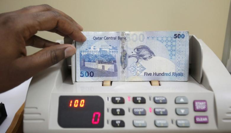 A cashier counts Qatari riyal notes at a money changer in Doha May 28, 2013. REUTERS/Fadi Al-Assaad