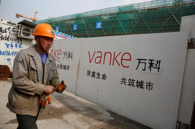 A person walks past by a gate with a sign of Vanke at a construction site in Shanghai, China, March 21, 2017. Picture taken March 21, 2017. REUTERS/Aly Song