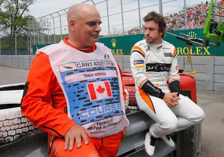 Formula One - F1 - Canadian Grand Prix - Montreal, Quebec, Canada  - 09/06/2017 - McLaren's Fernando Alonso (R) sits on a barricade after experiencing mechanical problems during the first free practice session. REUTERS/Chris Wattie