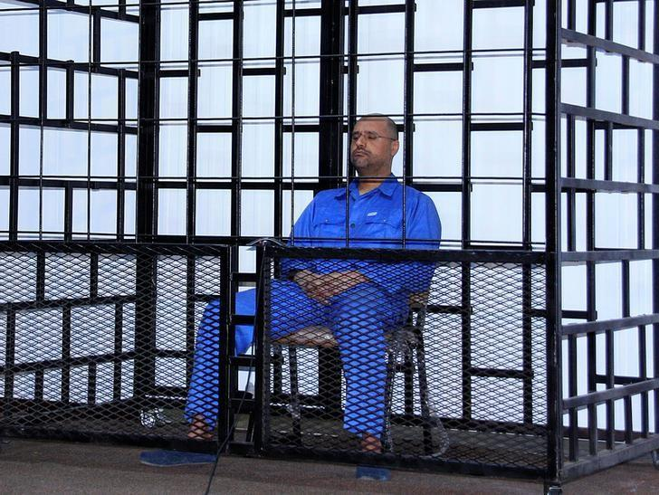 FILE PHOTO: Saif al-Islam Gaddafi, son of late Libyan leader Muammar Gaddafi, attends a hearing behind bars in a courtroom in Zintan May 25, 2014. REUTERS/Stringer/File Photo