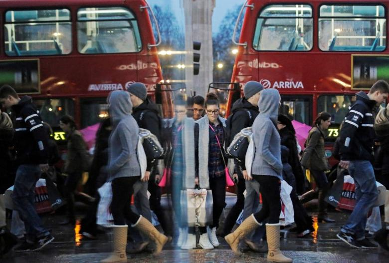 FILE PHOTO:  Shoppers are reflected in a shop window as they walk along Oxford Street in London, Britain, December 21, 2013.   REUTERS/Luke MacGregor/File Photo
