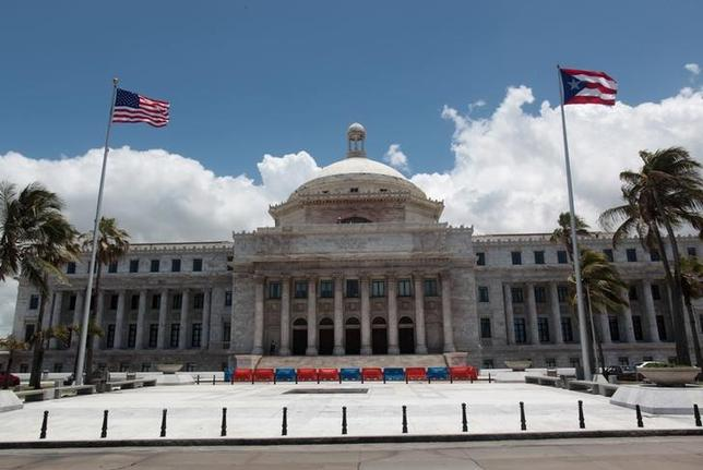 FILE PHOTO: The flags of the U.S. and Puerto Rico fly outside the Capitol building in San Juan, Puerto Rico May 4, 2017. REUTERS/ Alvin Baez