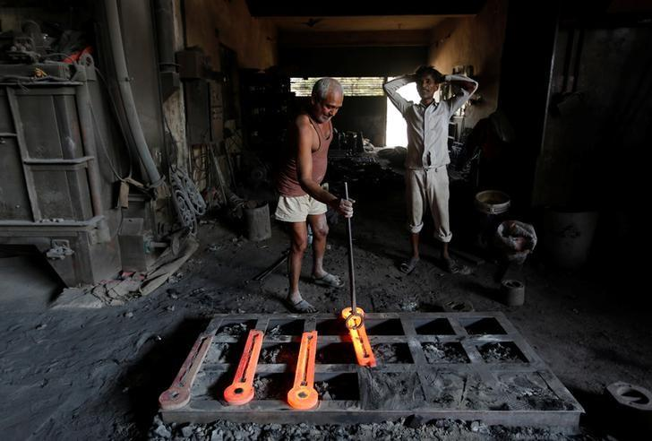 A worker makes parts for lamp posts inside an iron casting factory in Ahmedabad, India March 1, 2017. REUTERS/Amit Dave/Files