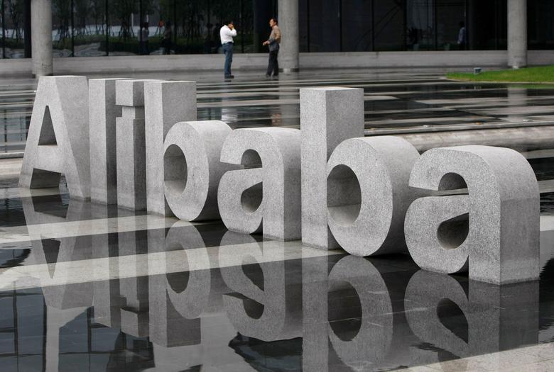 FILE PHOTO: Two men chat beside a logo of Alibaba (China) Technology Co. Ltd at its headquarters on the outskirts of Hangzhou, Zhejiang province May 17, 2010.  REUTERS/Steven Shi/File Photo