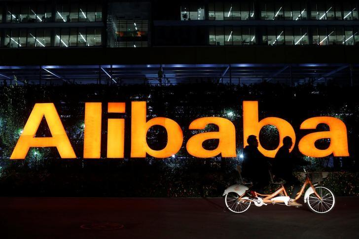 People ride a double bicycle past the Alibaba Group logo, at the company's headquarters, on the outskirts of Hangzhou, China November 10, 2014. REUTERS/Aly Song/File Photo