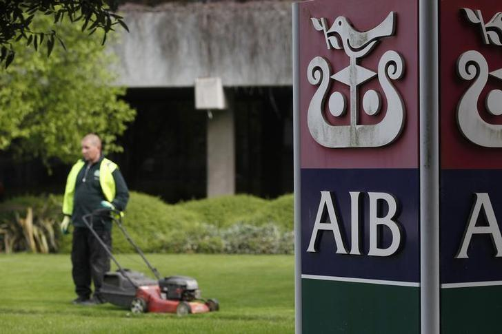 FILE PHOTO: A gardener mows the grass outside the headquarters of AIB on the day the bank announced it's results, in Dublin April 12, 2011.  REUTERS/Cathal McNaughton