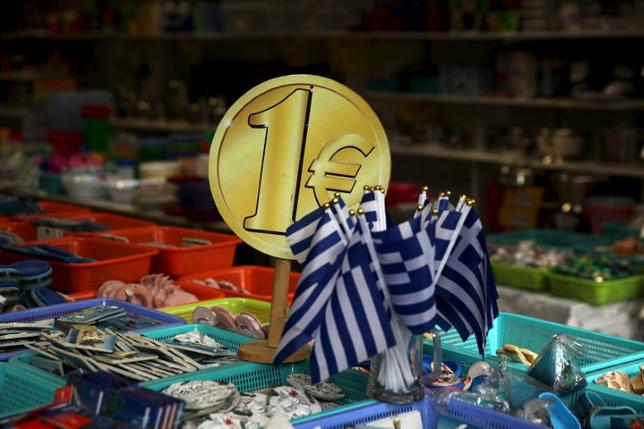 6月12日、複数の当局筋によると、ギリシャ支援をめぐりユーロ圏財務相(ユーログループ)と国際通貨基金(IMF)が15日の会合で妥協する公算が大きい。写真は1ユーロ硬貨の模型とギリシャ国旗。アテネの土産店で2015年7月撮影(2017年 ロイター/Yiannis Kourtoglou)