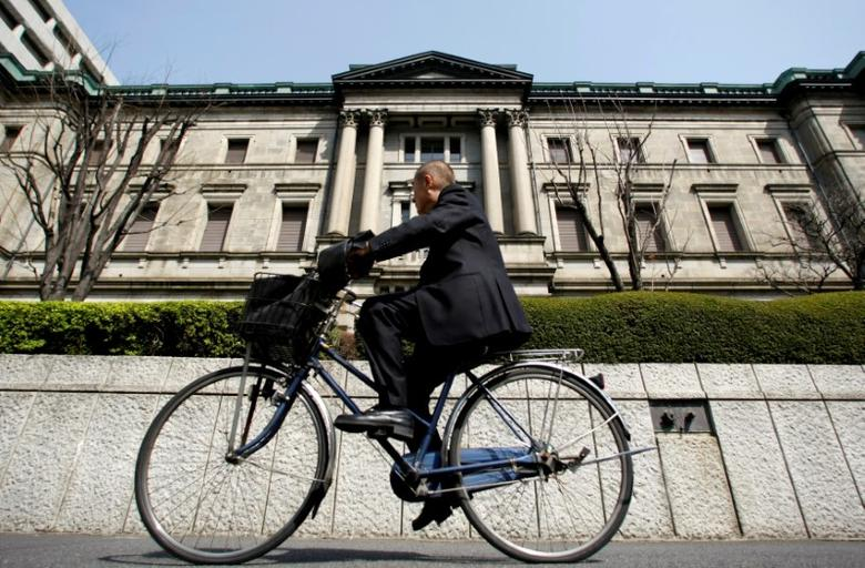 FILE PHOTO: A man rides a bicycle past the Bank of Japan (BOJ) building in Tokyo, Japan March 18, 2009. REUTERS/Yuriko Nakao/File Photo