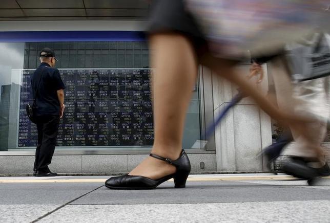 6月13日、前場の東京株式市場で、日経平均株価は前日比22円86銭安の1万9885円72銭となり小幅に続落した。写真は株価ボードを眺める男性、2015年8月撮影(2017年 ロイター/Yuya Shino)