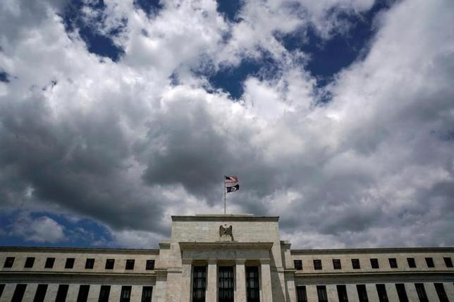 Flags fly over the Federal Reserve Headquarters on a windy day in Washington, U.S., May 26, 2017. REUTERS/Kevin Lamarque/Files