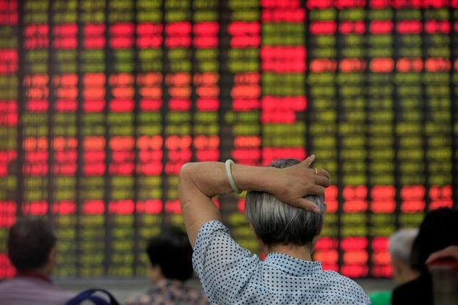 6月12日、株価指数の開発・算出を手掛ける米MSCIは近く、中国本土に上場している人民元建て株式(A株)を新興国株指数に組み入れる可能性があるが、まだA株を巡る問題は解消されていない。写真は、証券会社の株価ボードを眺める投資家。上海で昨年6月撮影(2017年 ロイター/Aly Song)