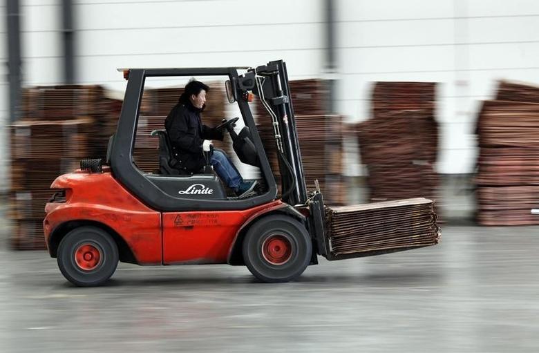 资料图片:2012年3月,上海洋山深水港附近仓库,一名工人在搬运铜板材。REUTERS/Carlos Barria