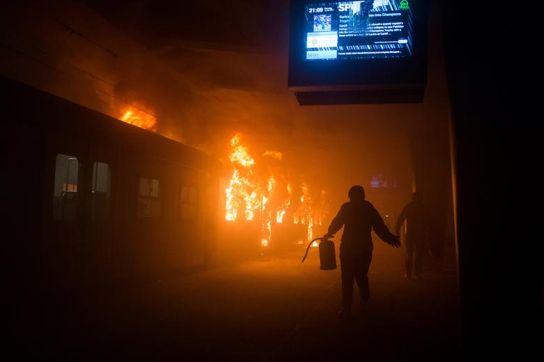 An official carries a fire extinguisher as train carriages burn at Cape Town station, South Africa, June 12, 2017. Protesters torched trains and smashed windows at Cape Town's central station on Monday in frustration over delayed travel services. Picture taken June 12, 2017. REUTERS/Ashraf Hendricks/GroundUp